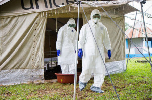 Health workers rinse their feet in bleach when leaving a tent for Ebola patients. Our blogger says the world should rinse out its prejudice and not repeat the same mistakes made with AIDS 30 years ago.