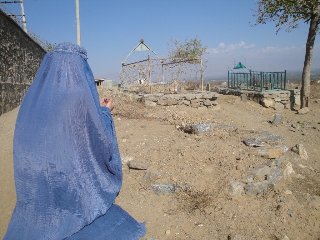 Zarmine (her back to the camera) prays in front of her brother Hashmatullah's grave. creidit: Sohaila Weda Khamoosh/Killid