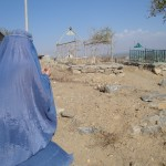 Zarmine (her back to the camera) prays in front of her brother Hashmatullah&#039;s grave.