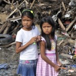 Two girls look out over debris in the Philippines following Typhoon Haiyan. Photo: Courtesy of Global Partnership for Effective Development Co-operation