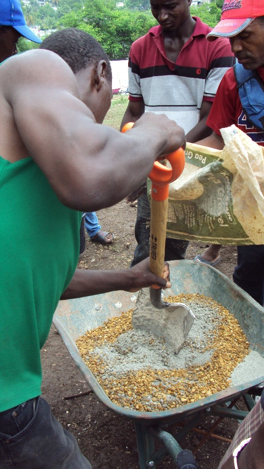 Mixing cement at Petionville Club camp.